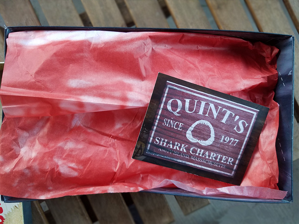 Bloody tissue paper and Quint's Shark Charter card.